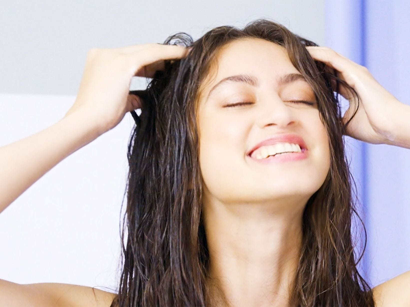 woman smiling washing her hair now she knows how often to shower