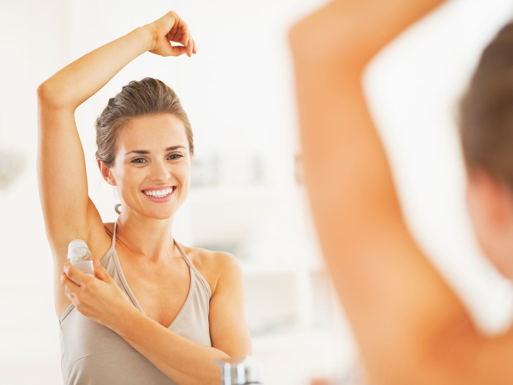 woman applying deodorant to stop excessive sweating
